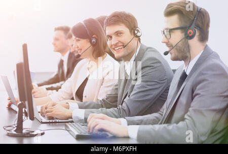 employee call center with headset at workplace - Stock Photo