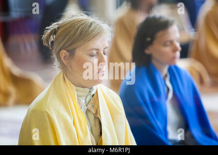 Close-up of two young women practising meditation in yoga class. - Stock Photo