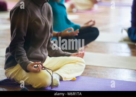 Yoga students practising meditation while sitting on their yoga mats in yoga class. - Stock Photo