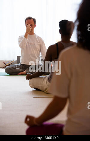 People practising meditation in yoga class with a yoga teacher. - Stock Photo