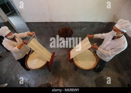 Suiyang. 6th Mar, 2018. Workers wind partly finished hollow noodles onto a wooden stand for further processing at - Stock Photo