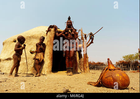 Himba woman with his kids in front of his hut near Epupa Falls, Namibia - Stock Photo