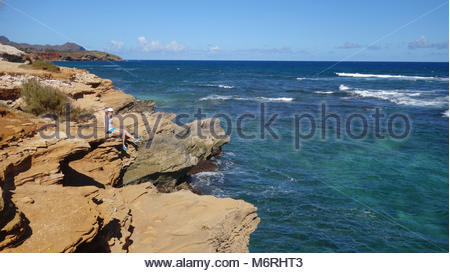 Smiling fearless girl sits on the cliff on Shipwreck beach in Kauai (HI, USA) - Stock Photo