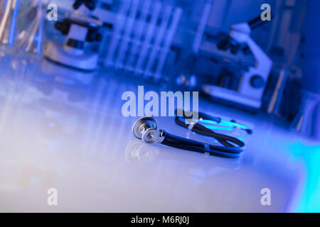 Stethoscope, microscope, laboratory background, lab glassware.  Blue background. Place for typography. - Stock Photo