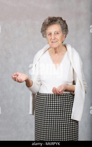 Senior woman between 70 and 80 years old is showing something - Stock Photo