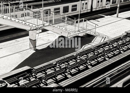 Trains and stair on platform top view at sunny summer day in black and white - Stock Photo