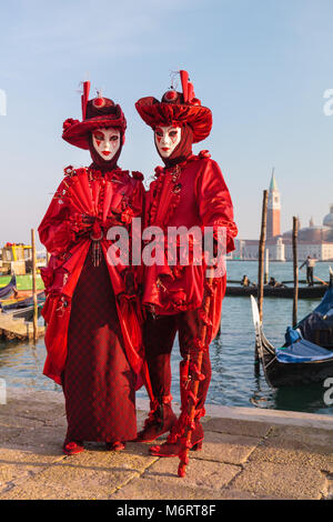 Couple in beautiful red fancy dress costumes and mask by the lagoon at the Venice Carnival, Carnivale di Venezia, - Stock Photo