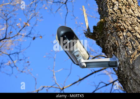 Zoom on a video surveillance camera with blue sky background - Stock Photo