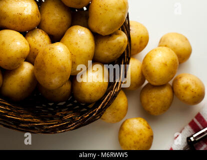 Within a wicker basket are several pounds of New Potatoes with peeler at side - Stock Photo