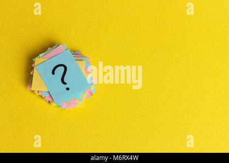 question marks written reminders tickets on yellow paper background. - Stock Photo