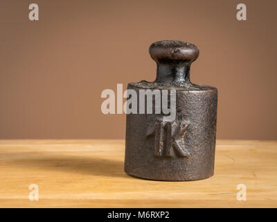 Old black iron 1kg weight for a kitchen scale standing on a table - Stock Photo