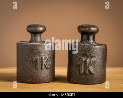 Old black iron 1kg weights for a kitchen scale standing on a table - Stock Photo