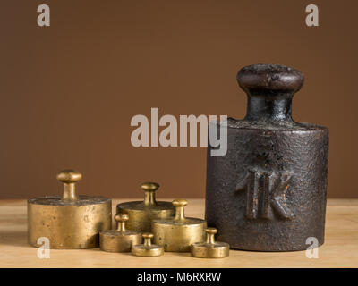 Old iron 1kg weight and smaller brass weights for a kitchen scale standing on a table - Stock Photo