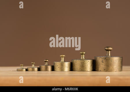 Old brass weights for a kitchen scale standing on a table - Stock Photo