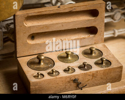 Old brass weights for a kitchen scale in a wooden box - Stock Photo