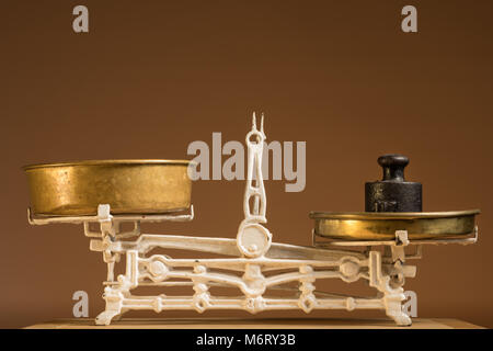 Old white vintage kitchen scale, brass with weights, brown background - Stock Photo