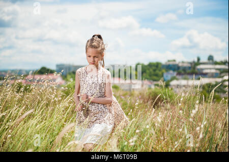 cute little girl goes through a field with a blue sky on a background - Stock Photo
