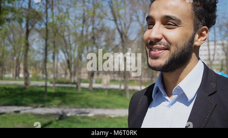 Trainee walking in park after work, smiling with dimples on face - Stock Photo