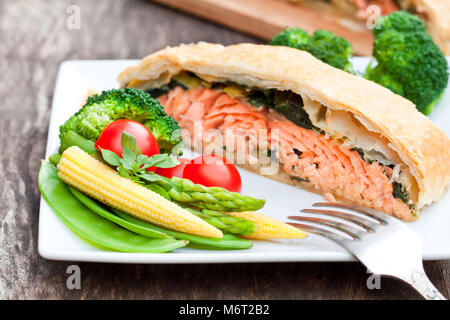 Salmon  fillet on leek and spinachbaked in puff pastry with vegetables - Stock Photo