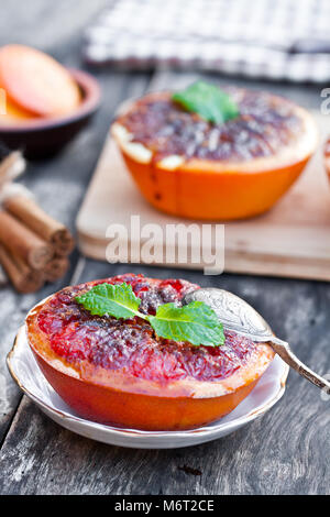 baked  grapefruit with brown sugar and cinnamon on a saucer - Stock Photo