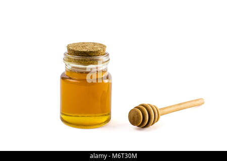 Honey in jar and wooden honey dipper isolated on white background with clipping path. - Stock Photo