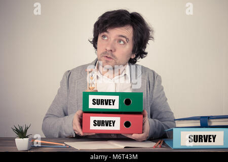 Survey text on the binders, worried bussinesman thinking by the work desk - Stock Photo
