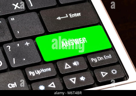 On the laptop keyboard the green button written ANSWER. - Stock Photo