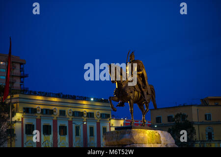 Albanian national hero monument Skanderbeg in Tirana city center illuminated by night - Stock Photo