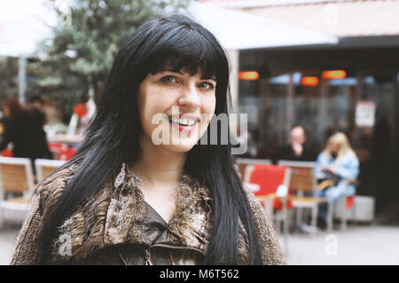 young woman in downtown pedestrian street in front of an outdoor cafe - Stock Photo