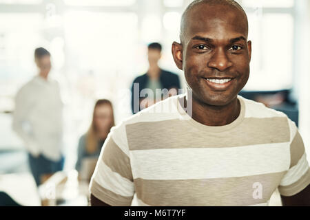 Young African designer smiling confidently while standing in an office with a group of colleagues working together - Stock Photo