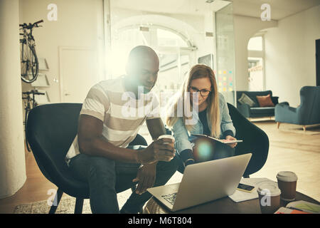 Two young designers smiling and working online together with a laptop while sitting in a stylish modern office - Stock Photo