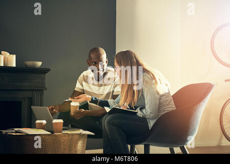 Two smiling design colleagues sitting and talking together while working online with a laptop in a stylish modern - Stock Photo