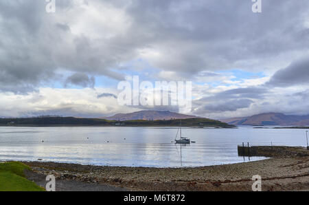 The View North from Port Appin looking towards the Isle of Lismore and the Mountains beyond. A Yacht lies moored - Stock Photo