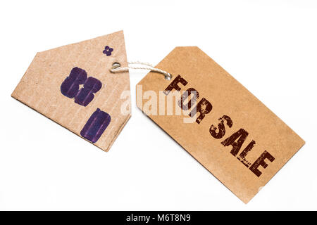 Small house with for sale sign on a white background. - Stock Photo