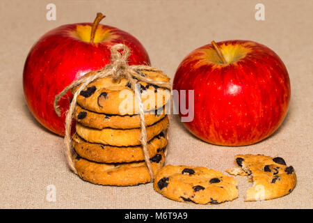Chocolate cookies and a red apple on background burlap. - Stock Photo