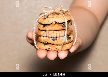 Hands hold chocolate cookies chocolate chip cookies tied up with a ribbon. - Stock Photo