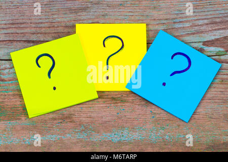 questions, decision making or uncertainty concept - a pile of colorful sticky notes with question marks on wooden - Stock Photo