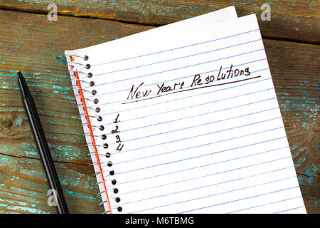 New Year's Resolution written on a notepad and pen. New Year resolutions concept. - Stock Photo