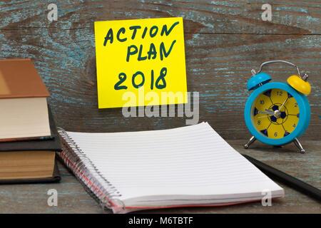 Action Plan 2018 Inscription written on sticky note. Books, pen, alarm clock, on wooden background. Business motivation,inspiration - Stock Photo