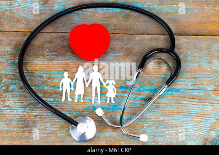 Paper silhouette of family, stethoscope and heart on wooden background. Health insurance concept. - Stock Photo