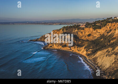Beautiful view of giant bluffs and homes of Flat Rock Point at sunset with coastline view of nearby South Bay beach - Stock Photo