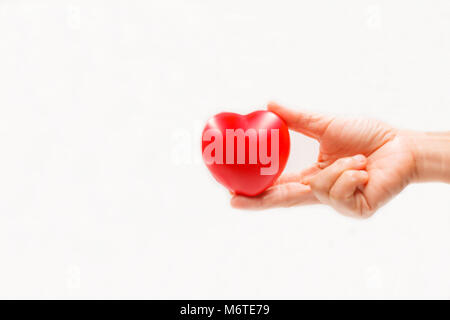 Heart shape in the helping hand on white background. Heart illness, disease protection, proactive checkup, mind - Stock Photo