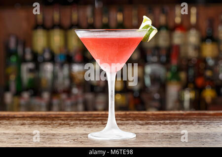 A cosmopolitan alcoholic cocktail is on the bar in a restaurant or in a club. Blurred background of alcohol. - Stock Photo