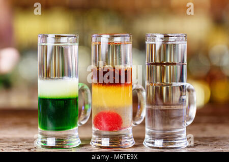 Multi-colored cocktails in a nightclub, alcoholic multi-layered cocktails - Stock Photo