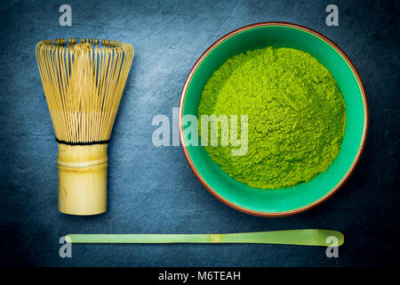 Matcha green tea powder in a bowl with bamboo whisk and spoon on dark slate background. - Stock Photo