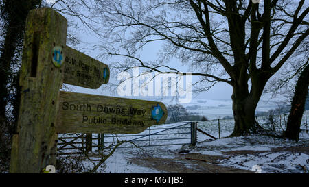 Snowy scene and sign post for South Downs way footpath on Old Winchester Hill on the South Downs near West Meon - Stock Photo