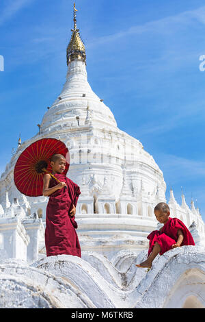 Young novice Buddhist monks, one holding parasol & one sitting at Myatheindan Pagoda (also known as Hsinbyume Pagoda), - Stock Photo