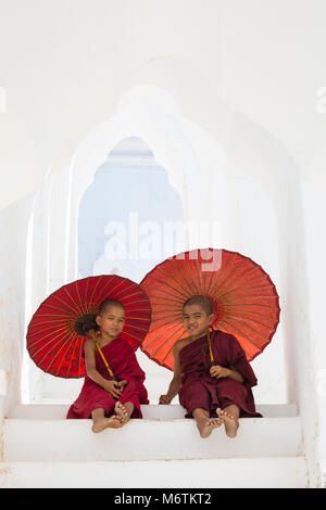Young novice Buddhist monks holding parasols at Myatheindan Pagoda (also known as Hsinbyume Pagoda), Mingun, Myanmar - Stock Photo