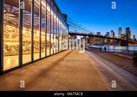 Brooklyn Bridge Park at twilight with view on the skyscrapers of Lower Manhattan, the Brooklyn Bridge and the carousel. - Stock Photo