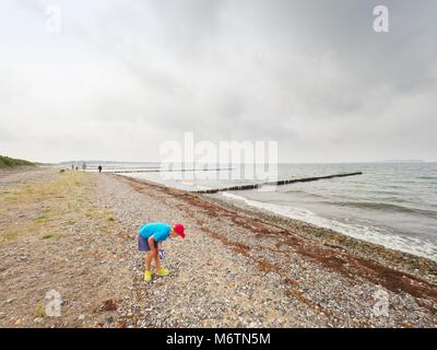 Blond boy on beach looking for shells.  Long stony beach with wooden breakwaters to protect a coast  from the force - Stock Photo
